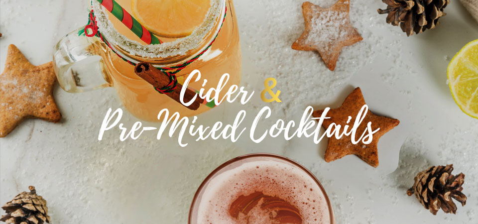 "A top view of mixed holiday drink in a mason jar on a table that is decorated with star-shaped cookies, pinecones and fake snow. Text that says ""Cider & Pre-Mixed Cocktails""."